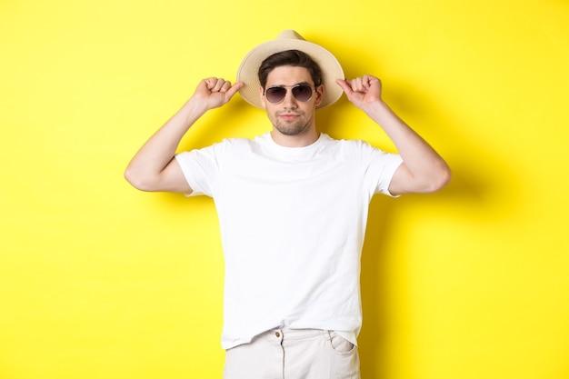 Zelfverzekerde jonge mannelijke toerist klaar voor vakantie, met strohoed en zonnebril, staande tegen een gele achtergrond.