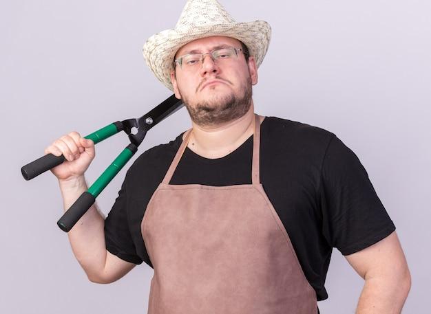 Zelfverzekerde jonge mannelijke tuinman die tuinieren hoed draagt ?? die tondeuse op schouder zet die op witte muur wordt geïsoleerd