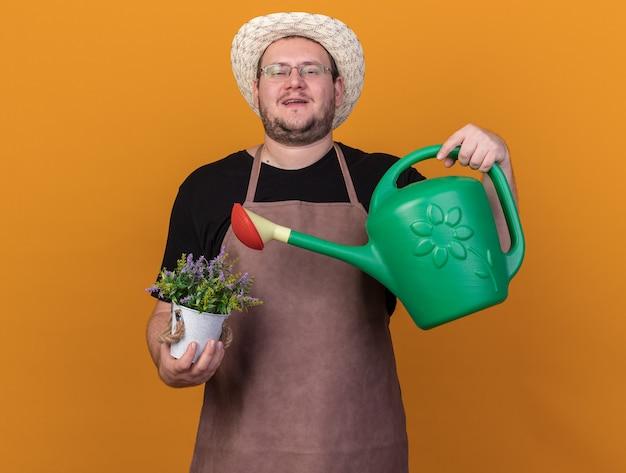 Zelfverzekerde jonge mannelijke tuinman met tuinhoed en handschoenen met gieter met bloem in bloempot geïsoleerd op oranje muur