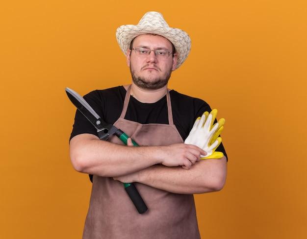 Zelfverzekerde jonge mannelijke tuinman tuinieren hoed houden en kruising handschoenen met tondeuse geïsoleerd op oranje muur dragen