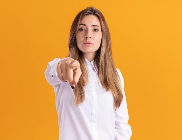 Zelfverzekerde jonge mooie blanke meisjespunten geïsoleerd op een oranje muur met kopieerruimte