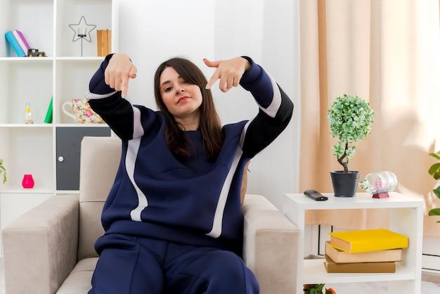 Zelfverzekerde jonge mooie blanke vrouw zittend op een stoel in ontworpen woonkamer op zoek en wijst
