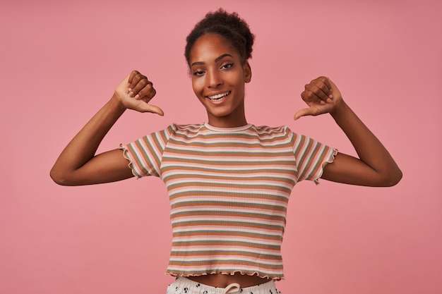 Zelfverzekerde jonge mooie bruinharige gekrulde dame die vrolijk naar zichzelf duimen en wijd lacht terwijl ze in vrijetijdskleding over de roze muur staat