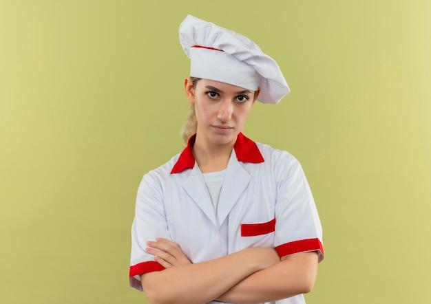 Zelfverzekerde jonge mooie kok in chef-kok uniform staande met gesloten houding geïsoleerd op groene muur green