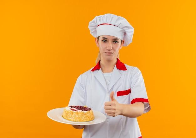 Zelfverzekerde jonge mooie kok in uniform van de chef-kok die een bord cake vasthoudt en duim omhoog laat zien, geïsoleerd op een oranje muur