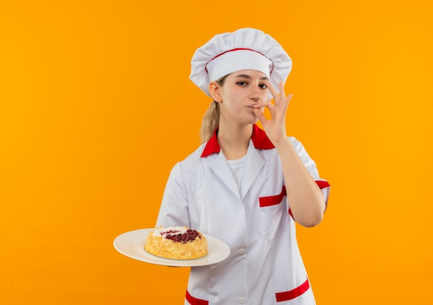 Zelfverzekerde jonge mooie kok in uniform van de chef-kok die een bord cake vasthoudt en een smakelijk gebaar doet dat op een oranje muur wordt geïsoleerd