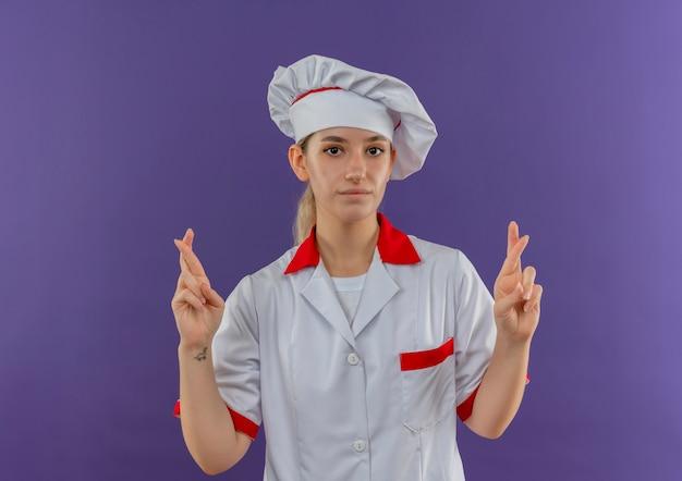 Zelfverzekerde jonge, mooie kok in uniform van de chef-kok die een gebaar met gekruiste vingers doet en er geïsoleerd uitziet op een paarse muur