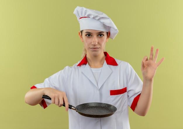 Zelfverzekerde jonge mooie kok in uniform van de chef-kok die een koekenpan vasthoudt die een goed teken doet dat op een groene muur is geïsoleerd