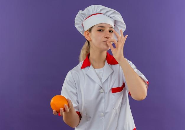 Zelfverzekerde jonge, mooie kok in uniform van de chef-kok die een smakelijk gebaar doet en oranje vasthoudt, geïsoleerd op een paarse muur