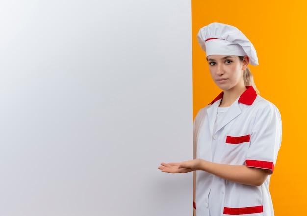Zelfverzekerde jonge mooie kok in uniform van de chef-kok die in de buurt staat en met de hand wijst naar een witte muur geïsoleerd op een oranje muur met kopieerruimte
