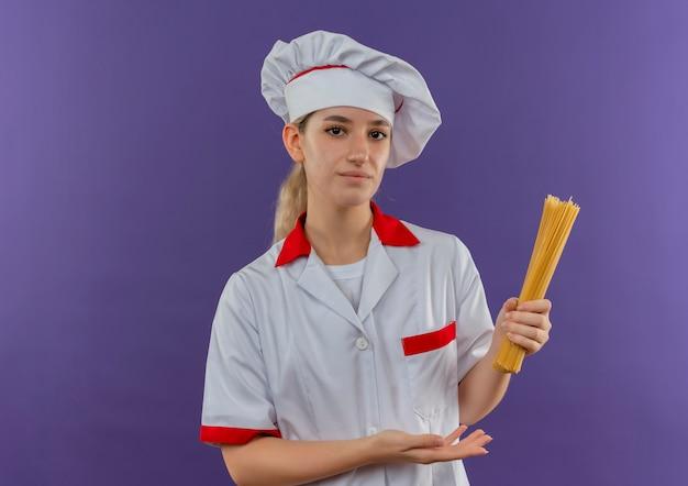 Zelfverzekerde jonge mooie kok in uniform van de chef-kok die met de hand wijst naar spaghetti pasta geïsoleerd op paarse muur