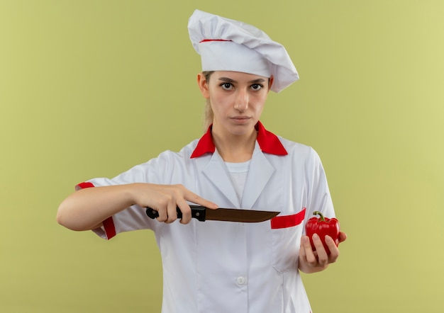 Zelfverzekerde jonge, mooie kok in uniform van de chef-kok die peper vasthoudt en met een mes naar hem wijst, geïsoleerd op een groene muur