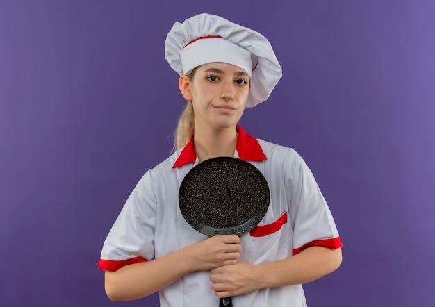 Zelfverzekerde jonge mooie kok in uniform van de chef-kok met koekenpan die geïsoleerd op paarse muur kijkt