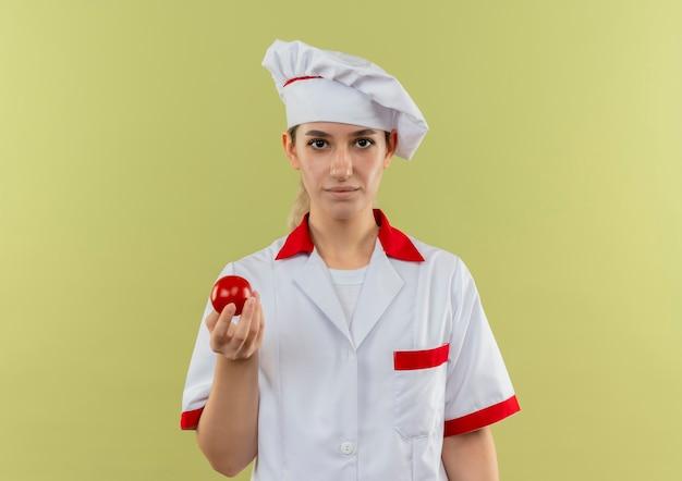 Zelfverzekerde jonge mooie kok in uniform van de chef-kok met tomaat geïsoleerd op groene muur