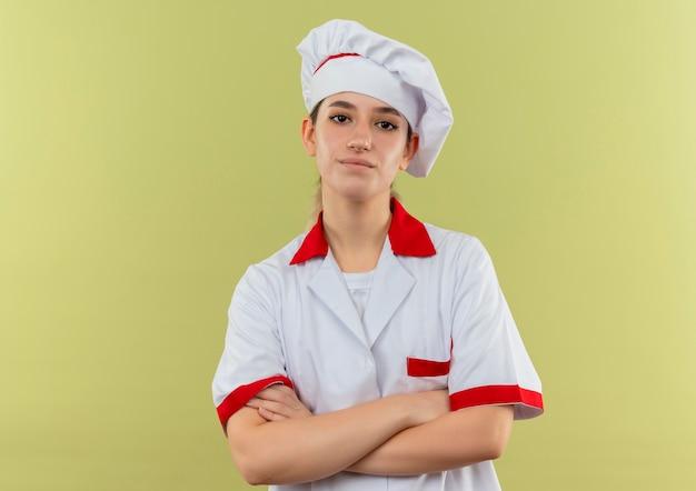 Zelfverzekerde jonge mooie kok in uniform van de chef-kok staande met gesloten houding geïsoleerd op groene muur met kopieerruimte