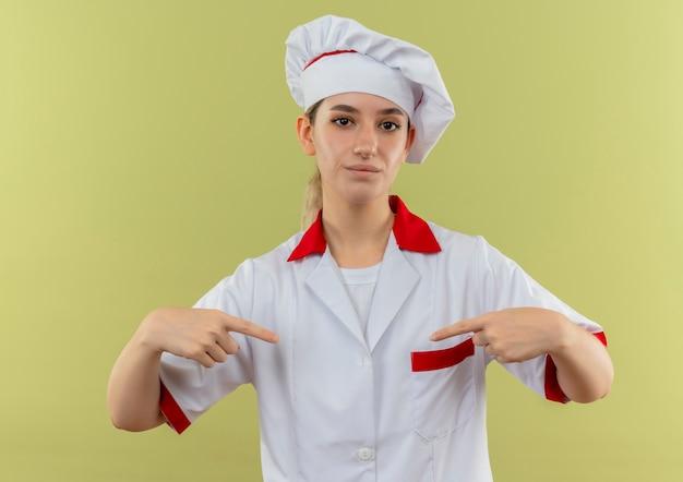 Zelfverzekerde jonge mooie kok in uniform van de chef-kok wijzend naar zichzelf geïsoleerd op groene muur