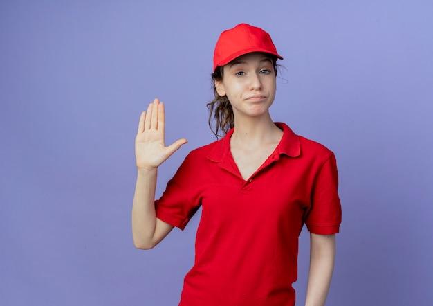 Zelfverzekerde jonge mooie leveringsvrouw die rode uniform en pet draagt die hallo gebaar doet