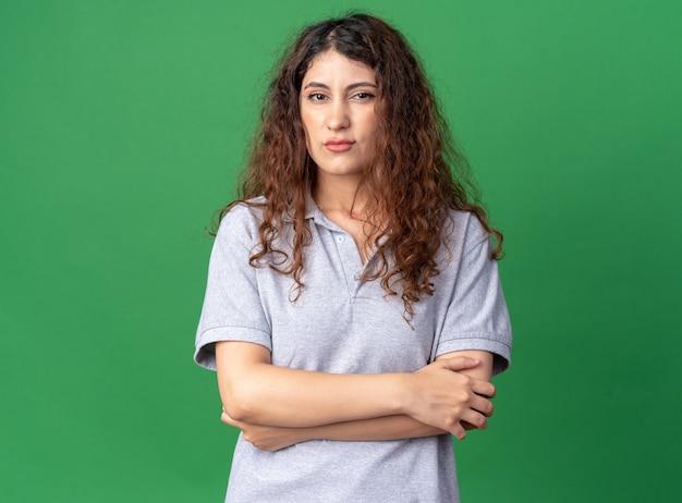 Zelfverzekerde jonge mooie vrouw die met gesloten houding naar de voorkant kijkt geïsoleerd op een groene muur met kopieerruimte