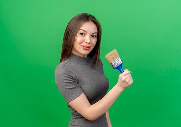 Zelfverzekerde jonge mooie vrouw die zich in de holdingsverfborstel van de profielmening bevindt die op groene achtergrond met exemplaarruimte wordt geïsoleerd