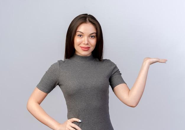 Zelfverzekerde jonge mooie vrouw hand op taille zetten en lege hand tonen geïsoleerd op een witte achtergrond