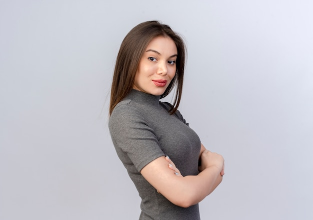 Zelfverzekerde jonge mooie vrouw in profiel te bekijken met gesloten houding geïsoleerd op een witte achtergrond met kopie ruimte