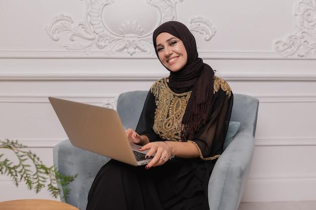 Zelfverzekerde jonge moslimvrouw kijkt thuis naar videobellen via webcamconferenties