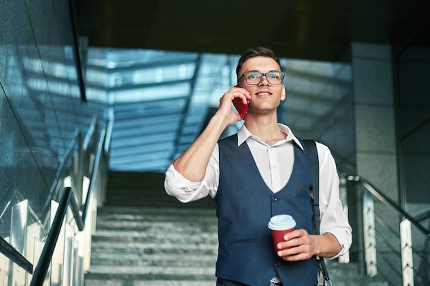 Zelfverzekerde jonge ondernemer praten op een smartphone