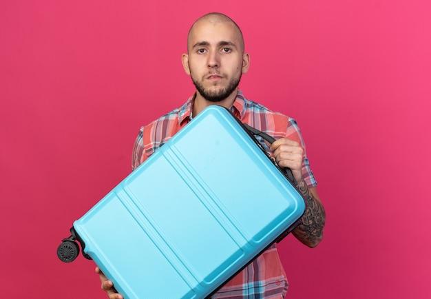Zelfverzekerde jonge reiziger man met koffer geïsoleerd op roze muur met kopieerruimte