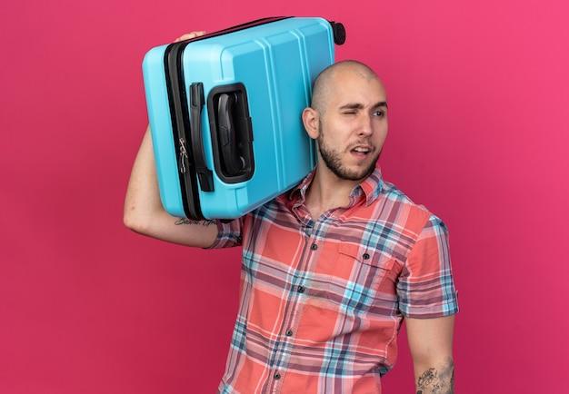 Zelfverzekerde jonge reiziger man met koffer op zijn schouder kijkend naar kant geïsoleerd op roze muur met kopieerruimte
