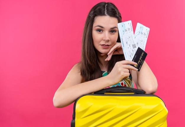 Zelfverzekerde jonge reizigersvrouw met koffer en kaartjes op geïsoleerde roze muur