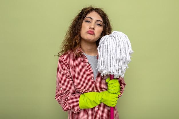 Zelfverzekerde jonge schoonmaakster die handschoenen draagt die mop houden