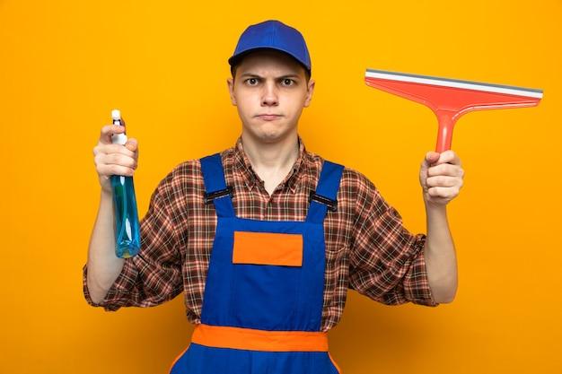 Zelfverzekerde jonge schoonmaakster met uniform en pet met reinigingsmiddel met dweilkop