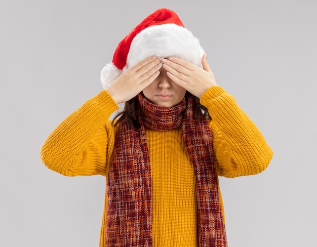 Zelfverzekerde jonge slavische meisje met kerstmuts en met sjaal om de nek ogen sluiten met handen geïsoleerd op een witte muur met kopie ruimte
