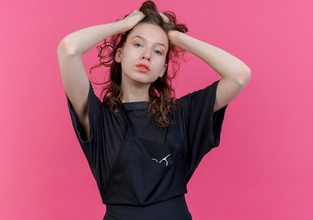 Zelfverzekerde jonge slavische vrouwelijke kapper dragen uniform haar haren grijpen kijken camera geïsoleerd op roze achtergrond