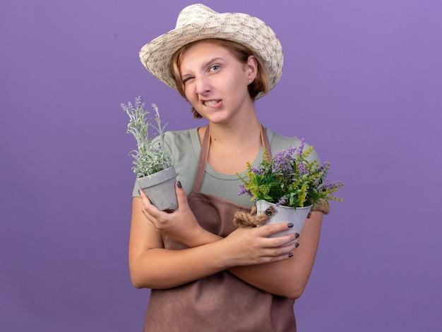 Zelfverzekerde jonge slavische vrouwelijke tuinman die tuinierende hoed draagt, knippert in het oog en houdt bloemen in bloempotten op paars