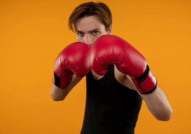 Zelfverzekerde jonge sportieve kerel die bokshandschoenen draagt die zich in de strijd bevinden stelt geïsoleerd op oranje muur