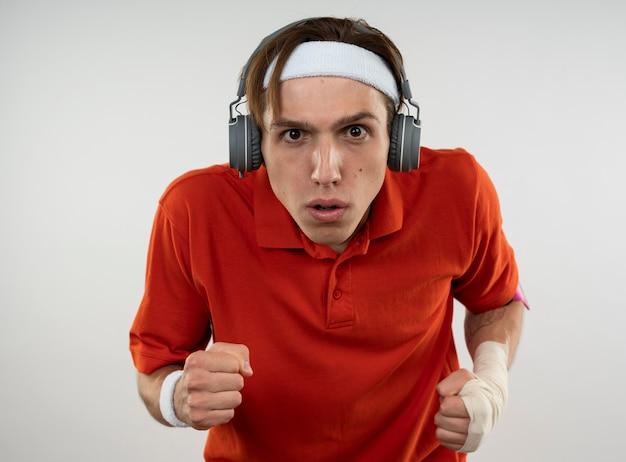 Zelfverzekerde jonge sportieve kerel die hoofdband met polsbandje en hoofdtelefoons met telefoonarmband draagt die lopend gebaar toont dat op witte muur wordt geïsoleerd