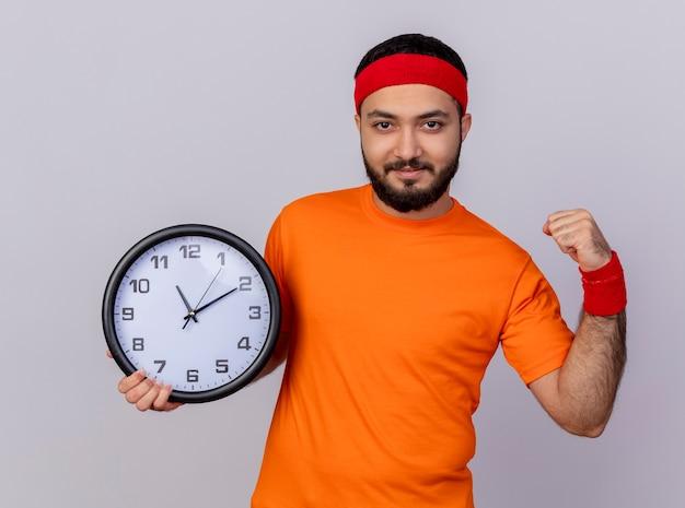 Zelfverzekerde jonge sportieve man met hoofdband en polsbandje houden wandklok met sterk gebaar geïsoleerd op een witte achtergrond