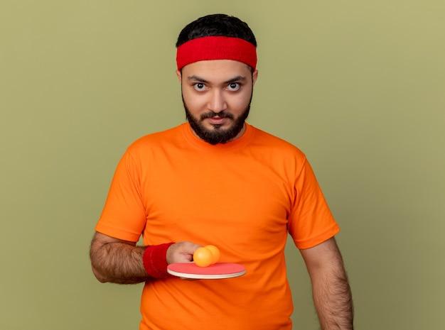 Zelfverzekerde jonge sportieve man met hoofdband en polsbandje met pingpongracket met bal geïsoleerd op olijfgroene achtergrond