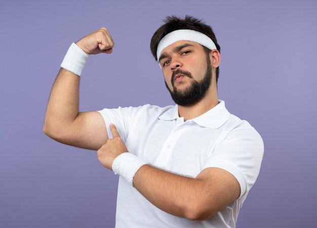Zelfverzekerde jonge sportieve man met hoofdband en polsbandje met sterk gebaar geïsoleerd op groene muur
