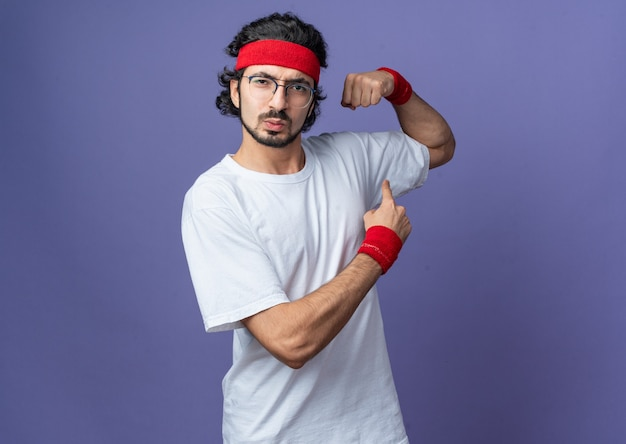 Zelfverzekerde jonge sportieve man met hoofdband met polsband die een sterk gebaar doet