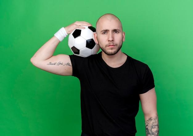 Zelfverzekerde jonge sportieve man met polsbandje bal op schouder zetten geïsoleerd op groene muur