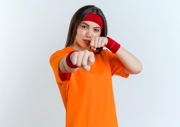 Zelfverzekerde jonge sportieve vrouw die hoofdband en polsbandjes draagt ?? die boksgebaar doet dat op witte muur met exemplaarruimte wordt geïsoleerd