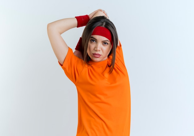Zelfverzekerde jonge sportieve vrouw die hoofdband en polsbandjes draagt die handen op rug en elleboog uitoefenen geïsoleerd op witte muur met exemplaarruimte