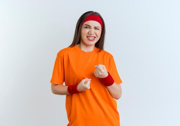 Zelfverzekerde jonge sportieve vrouw die hoofdband en polsbandjes draagt die vuisten balde op zoek geïsoleerd