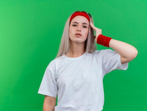 Zelfverzekerde jonge sportieve vrouw met beugels dragen hoofdband en polsbandjes legt hand op tempel geïsoleerd op groene muur