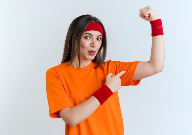 Zelfverzekerde jonge sportieve vrouw met hoofdband en polsbandjes doet sterk gebaar wijzend op haar spieren geïsoleerd op een witte muur met kopie ruimte