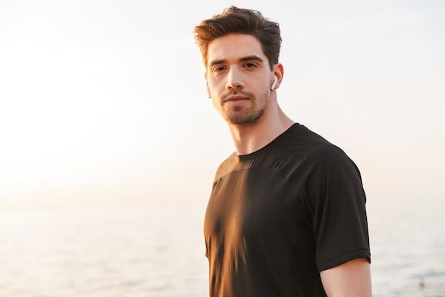 Zelfverzekerde jonge sportman in zwart overhemd