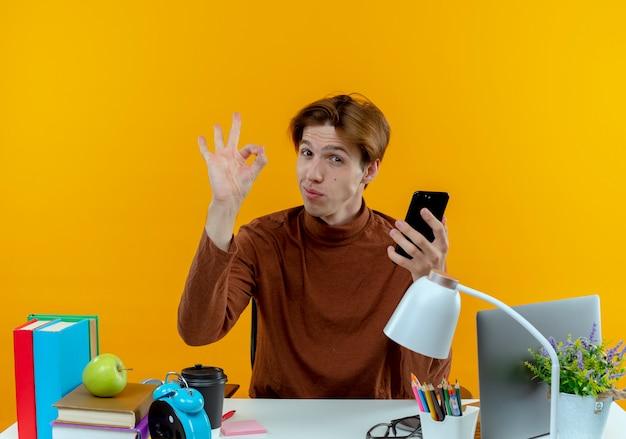 Zelfverzekerde jonge studentenjongen zittend aan een bureau met schoolhulpmiddelen die okey gebaar tonen en telefoon vasthouden