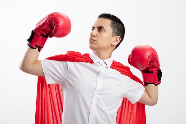 Zelfverzekerde jonge superheld jongen in rode cape doos handschoenen doen sterk gebaar kijken naar zijn hand geïsoleerd op een witte achtergrond